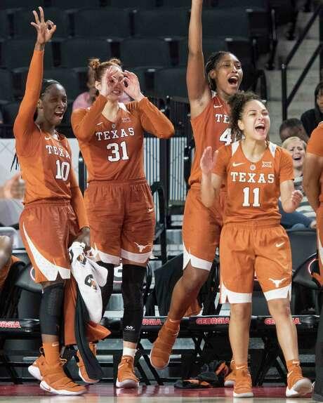 Texas' Lashann Higgs (10), Audrey-Ann Caron-Goudreau (31), Jatarie White and Brooke McCarty (11) celebrate a basket late in Sunday's win at Georgia. Photo: John Amis, FRE / FR69715 AP