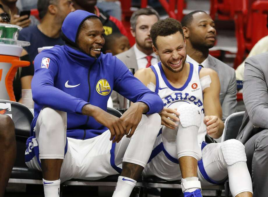 Golden State Warriors' Stephen Curry, right, and Kevin Durant react on the bench late in the fourth quarter against the Miami Heat in an NBA basketball game Sunday, Dec. 3, 2017, in Miami. The Warriors won 123-95. (AP Photo/Joe Skipper) Photo: Joe Skipper, Associated Press