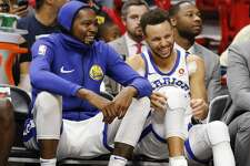 Golden State Warriors' Stephen Curry, right, and Kevin Durant react on the bench late in the fourth quarter against the Miami Heat in an NBA basketball game Sunday, Dec. 3, 2017, in Miami. The Warriors won 123-95. (AP Photo/Joe Skipper)