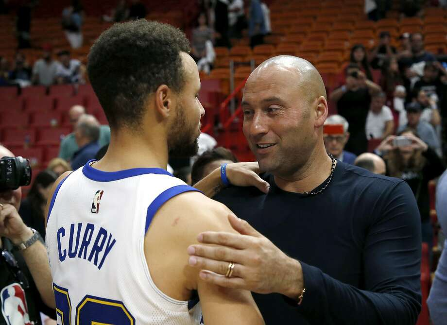 Derek Jeter, chief executive officer and part owner of the Miami Marlins and a former New York Yankee, speaks with Golden State Warriors guard Stephen Curry after the Warriors defeated the Miami Heat 123-95 in an NBA basketball game, Sunday, Dec. 3, 2017, in Miami. (AP Photo/Joe Skipper) Photo: Joe Skipper, Associated Press