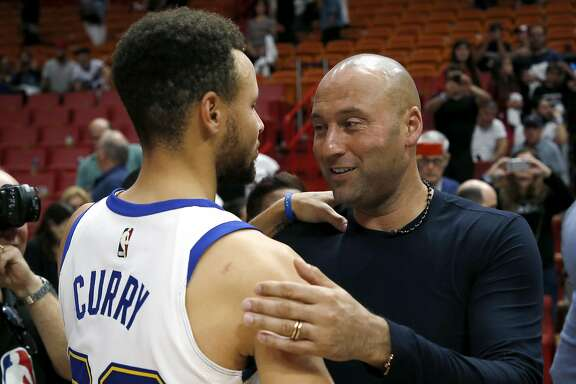 Derek Jeter, chief executive officer and part owner of the Miami Marlins and a former New York Yankee, speaks with Golden State Warriors guard Stephen Curry after the Warriors defeated the Miami Heat 123-95 in an NBA basketball game, Sunday, Dec. 3, 2017, in Miami. (AP Photo/Joe Skipper)