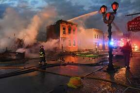 Firefighters from around the region work to control a multi-structure fire on Remsen Street on Thursday, Nov. 30, 2017 in Cohoes, N.Y.