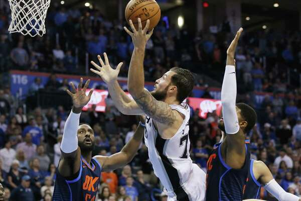 San Antonio Spurs center Joffrey Lauvergne, center, shoots between Oklahoma City Thunder forward Patrick Patterson (54) and forward Paul George, right, during the fourth quarter of an NBA basketball game in Oklahoma City, Sunday, Dec. 3, 2017. Oklahoma City won 90-87. (AP Photo/Sue Ogrocki)