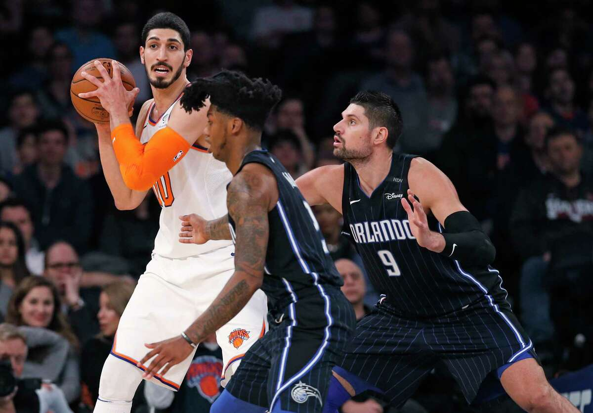 New York Knicks center Enes Kanter (00) looks to pass the ball as Orlando Magic guard Elfrid Payton, center, and center Nikola Vucevic (9) defend during the first half of an NBA basketball game in New York, Sunday, Dec. 3, 2017. The Magic defeated the Knicks 105-100. (AP Photo/Kathy Willens) ORG XMIT: MSG114