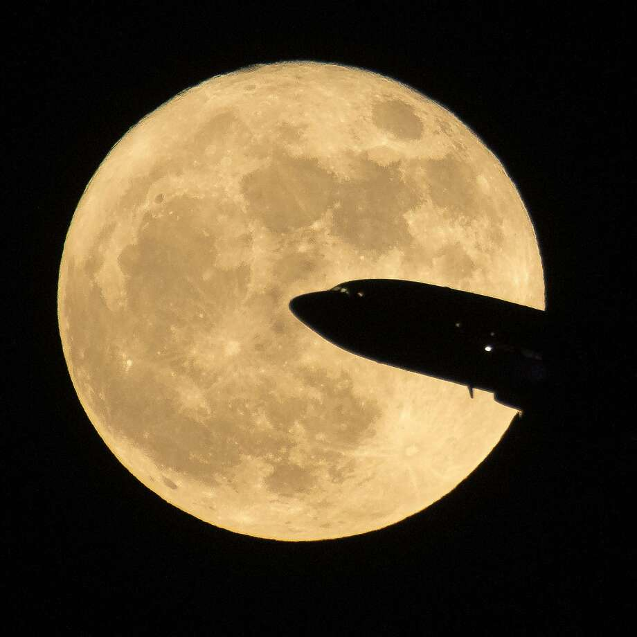 In this handout provided by NASA, an aircraft taking off from Ronald Reagan National Airport is seen passing in front of the moon as it rises on December 3, 2017 in Washington, DC.  Today's full Moon is the first of three consecutive supermoons. The two will occur on Jan. 1 and Jan. 31, 2018. A supermoon occurs when the moon's orbit is closest (perigee) to Earth at the same time it is full. (Photo by NASA/Bill Ingalls via Getty Images) Photo: Bill Ingalls/NASA, Getty Images