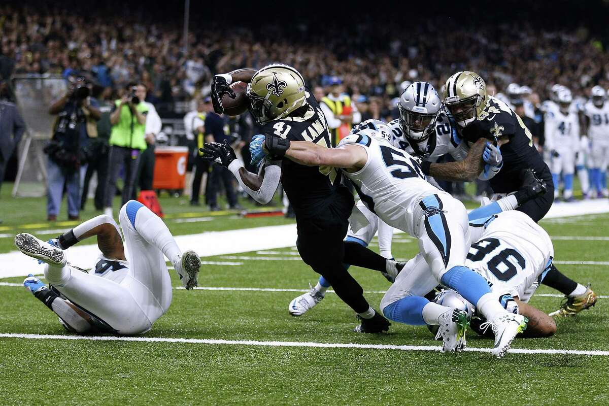 NEW ORLEANS, LA - DECEMBER 03: Alvin Kamara #41 of the New Orleans Saints scores a touchdown as Luke Kuechly #59 of the Carolina Panthers defends during the first half of a game at the Mercedes-Benz Superdome on December 3, 2017 in New Orleans, Louisiana. (Photo by Jonathan Bachman/Getty Images) ORG XMIT: 700070773