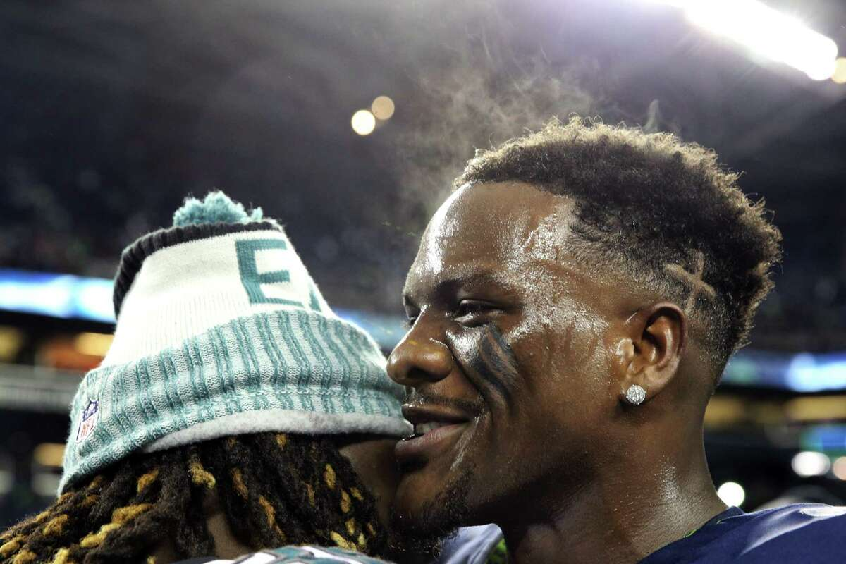 Seahawks defensive lineman Frank Clark talks with Eagles players after their game, Sunday, Dec. 3, 2017, at CenturyLink Field. (Genna Martin/seattlepi.com)