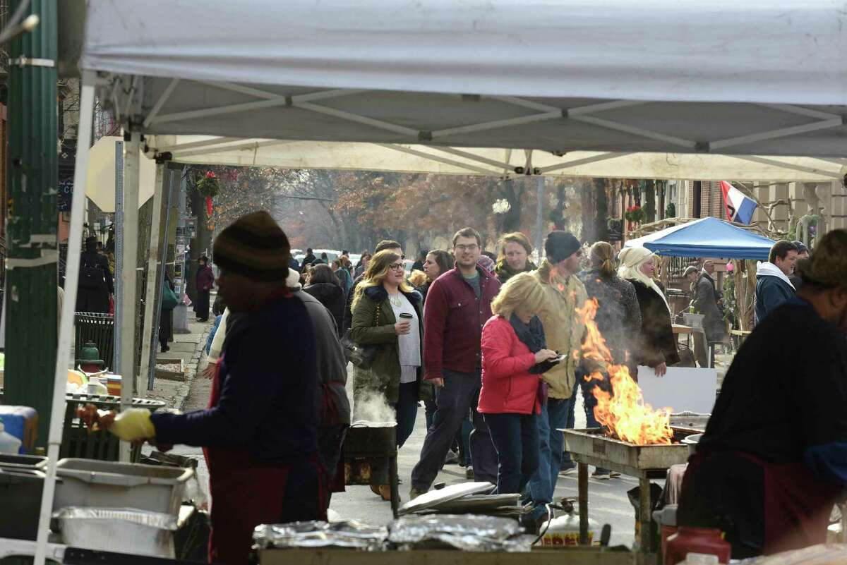People make their way through the streets as food vendors prepare food at the 35th Annual Troy Victorian Stroll on Sunday, Dec. 3, 2017, in Troy, N.Y. (Paul Buckowski / Times Union)