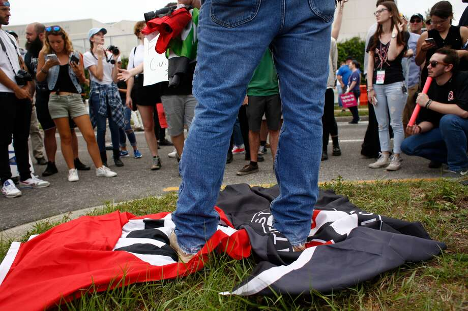 "A demonstrator at the University of Florida stands on a Nazi flag and an ""antifa,"" or ""anti-fascist"" flag. Photo: Brian Blanco / Getty Images"