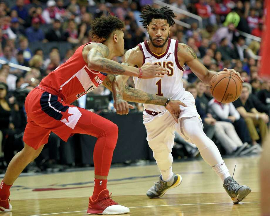 FILE - In this Nov. 3, 2017, file photo, Cleveland Cavaliers' Derrick Rose (1) dribbles against Washington Wizards forward Kelly Oubre Jr., left, during the first half of an NBA basketball game in Washington. Cavaliers coach Tyronn Lue says the team's communication with embattled point guard Rose has been positive. Rose is away from the team because of a personal matter. He also has been sidelined by a sprained left ankle. Photo: Nick Wass, AP / FR67404 AP