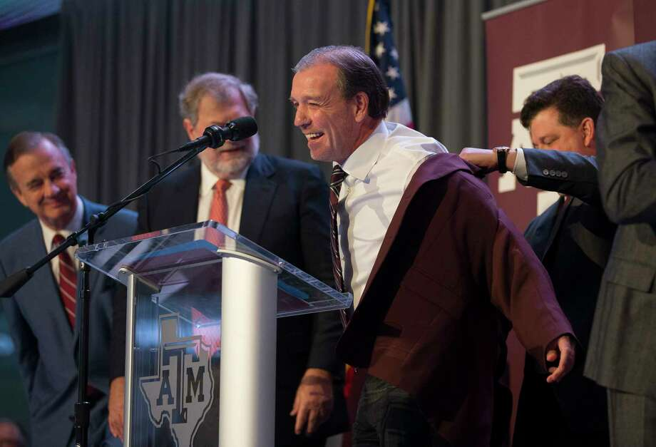 New Texas A&M University head football coach Jimbo Fisher is presented with a maroon jacket by athletic director Scott Woodward during a press conference at the school's Hall of Champions at Kyle Field, Monday, Dec. 4, 2017, in College Station.For more photos from the official press conference on Monday, browse through the gallery. Photo: Mark Mulligan, Houston Chronicle / © 2017 Houston Chronicle