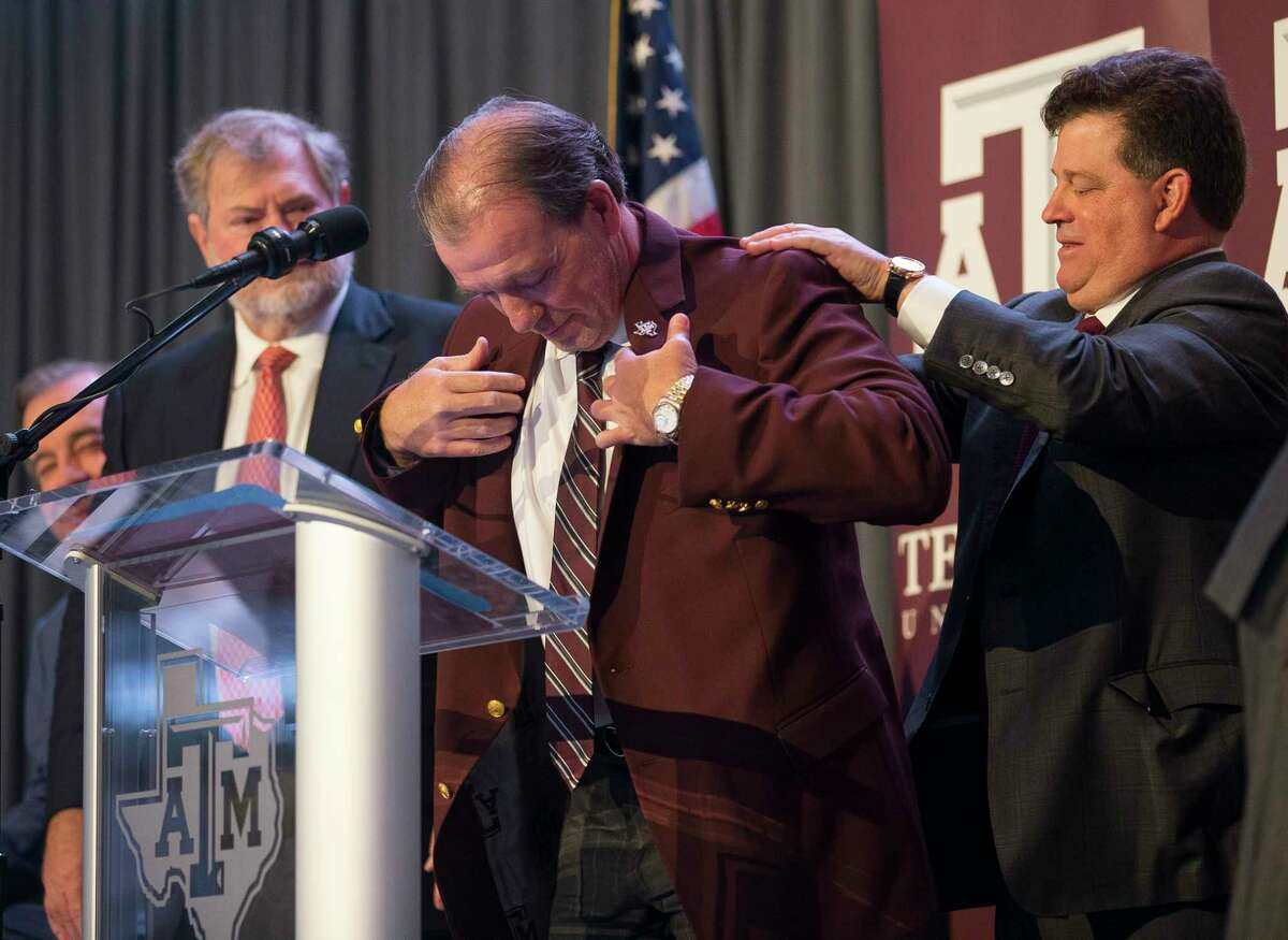 New Texas A&M University head football coach Jimbo Fisher is presented with a maroon jacket by athletic director Scott Woodward during a press conference at the school's Hall of Champions at Kyle Field, Monday, Dec. 4, 2017, in College Station.