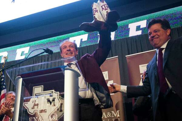 New Texas A&M University head football coach Jimbo Fisher is presented with Texas A&M cowboy boots by athletic director Scott Woodward during a press conference at the school's Hall of Champions at Kyle Field, Monday, Dec. 4, 2017, in College Station.