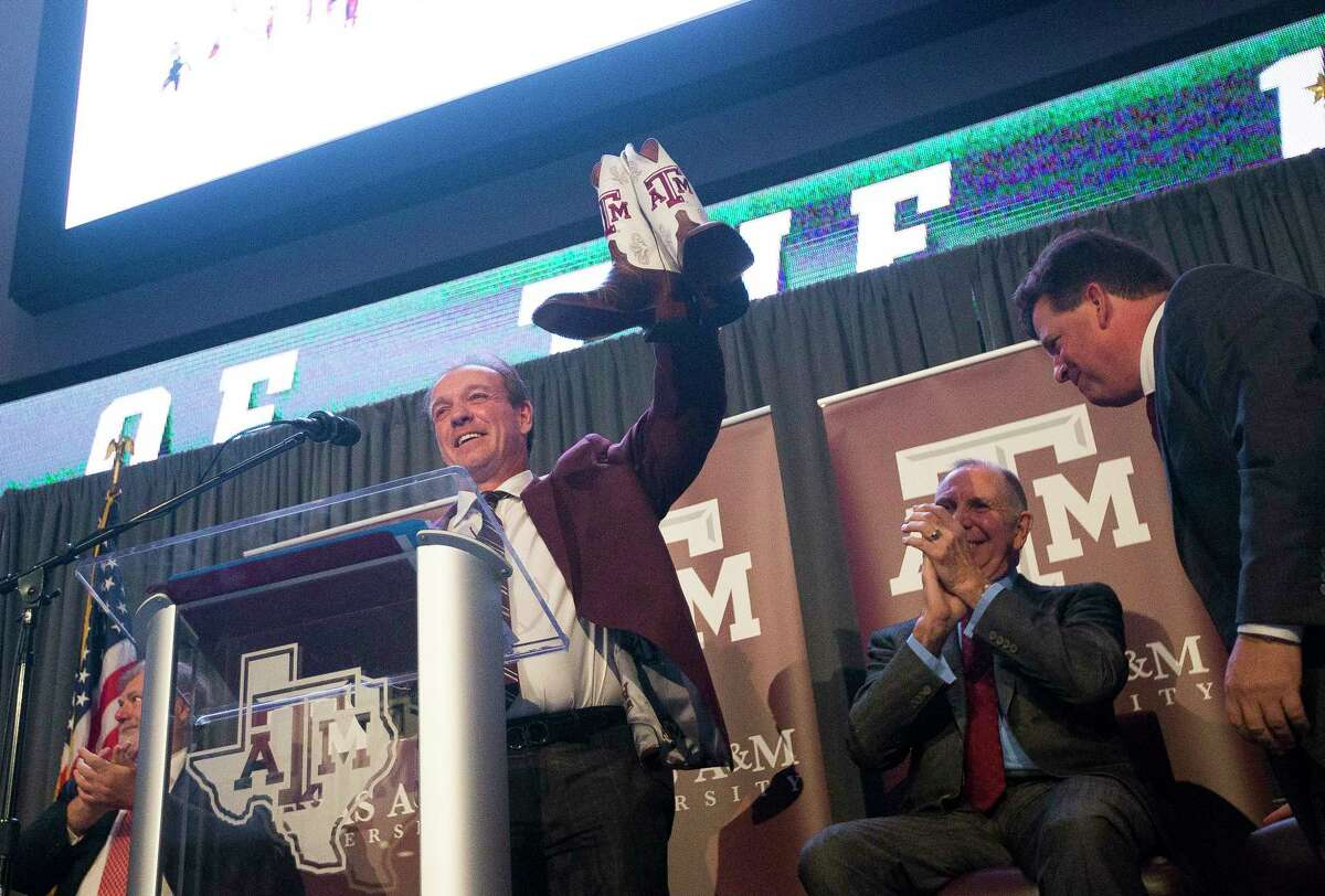 New Texas A&M University head football coach Jimbo Fisher is presented with Texas A&M cowboy boots during a press conference at the school's Hall of Champions at Kyle Field, Monday, Dec. 4, 2017, in College Station.