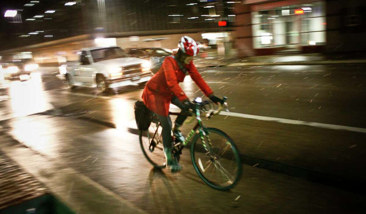 A bike rider navigates the streets during the unseasonable snow fall in downtown Houston, TX Wednesday, Dec. 10, 2008.