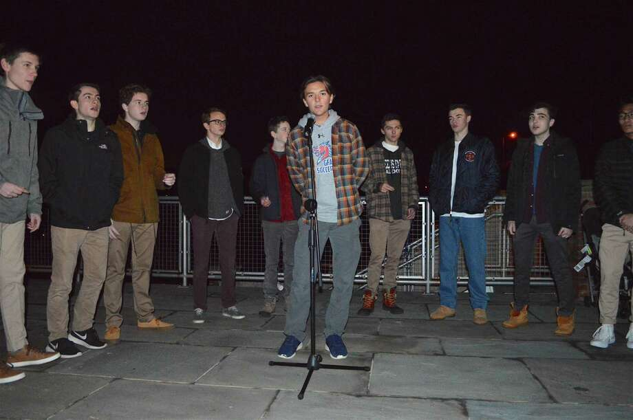 At right, The Beachers, a singing ensemble from Greens Farms Academy, led by Liam Murphy, 16, of Westport, perform at the annual tree lighting on Dec. 4. Photo: Jarret Liotta / For Hearst Connecticut Media / Westport News Freelance