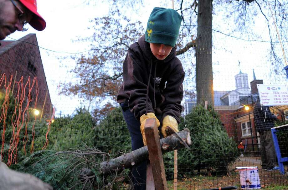 Tom Spisak, left, supervises as scout Owen Jacobson, 11, cuts the truck of a Christmas tree for a customer during Boy Scout Troop 82's 52nd annual Christmas Tree Sale at The First Church Congregational in Fairfield, Conn., on Saturday Dec. 2, 2017. The sale is open Thursdays and Fridays, 6-9 p.m., Saturdays, 9 a.m.-8 p.m. and Sundays, 11 a.m.-5 p.m. and runs through Sunday, Dec. 17th. All trees, wreaths and bows sold help fund the troop and its community service projects throughout the year. Photo: Christian Abraham / Hearst Connecticut Media / Connecticut Post