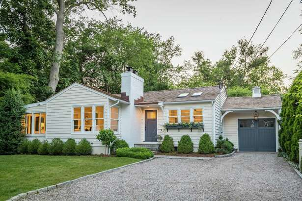 The buttercream-colored brick and wood bungalow at 8 Brookside Park sits at the end of an enchanting cul-de-sac.