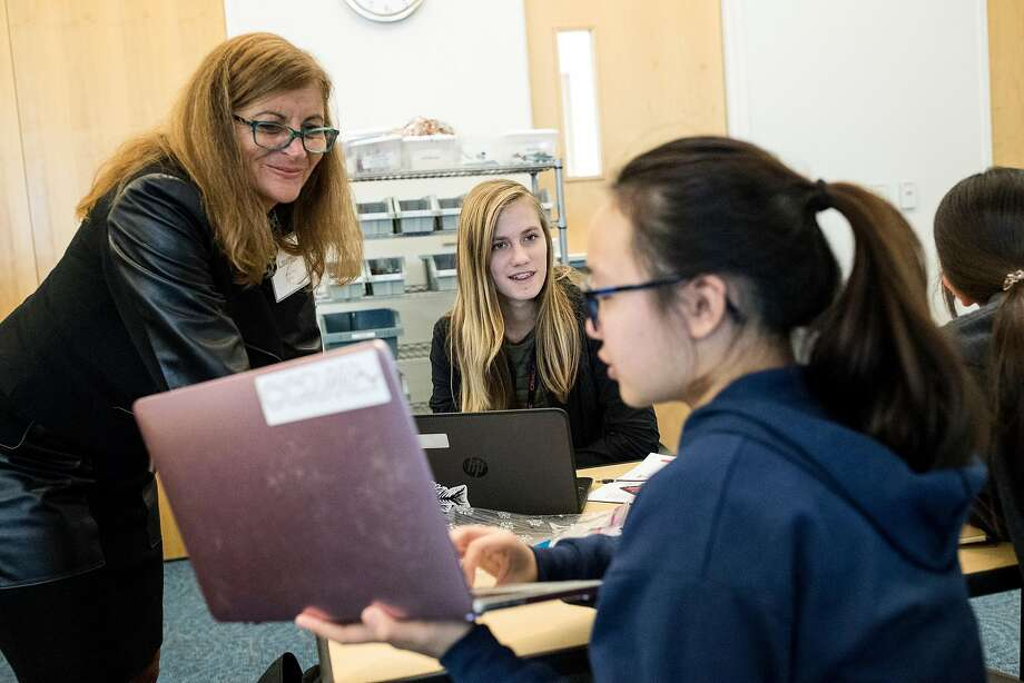 Lauren Diehl, a volunteer coach from Oracle, works with students Katie Brewster (center) and Adelyn Chen from public charter Design Tech High School, at the company's Redwood Shores campus. Photo: LAURA MORTON, NYT