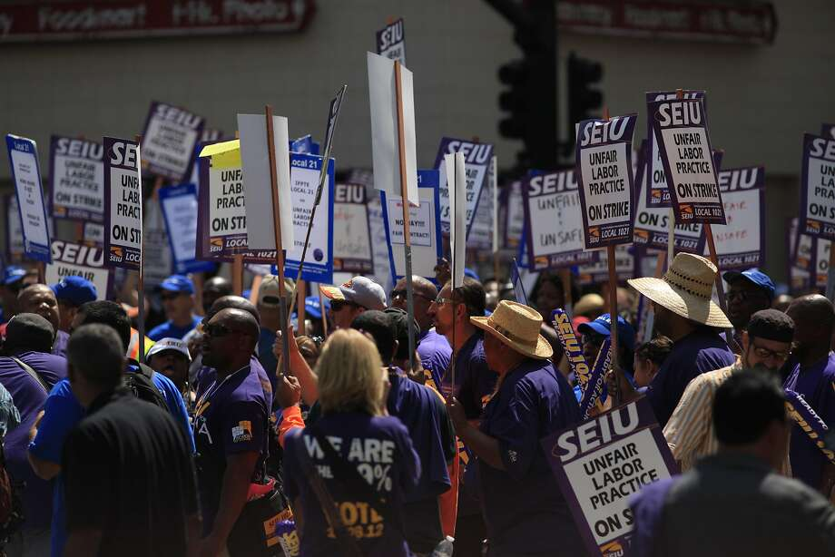 Blocking the street to traffic, SEIU 1021 union members comprised of BART and City of Oakland workers on strike today at Frank Ogawa Plaza on Monday July 1, 2013 in Oakland, Calif. Workers say they are protesting unfair labor practices and demand greater investment in critical public services. Photo: Mike Kepka, The Chronicle