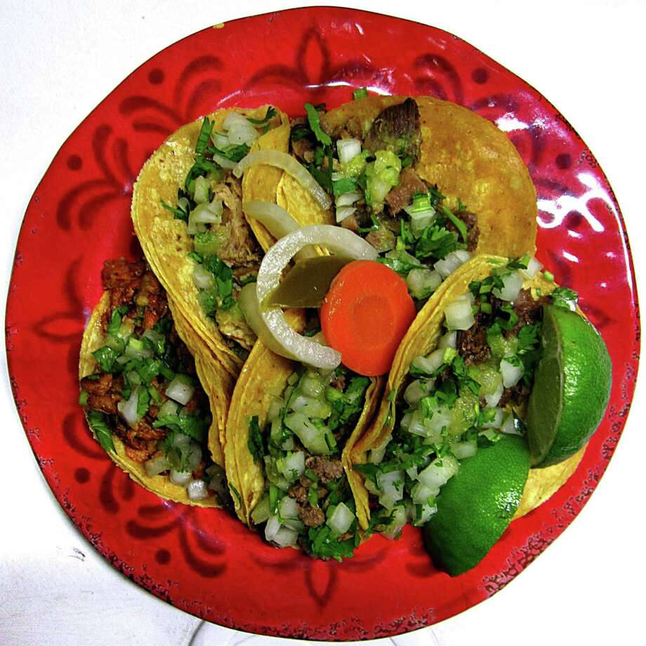 Five $1 dollar tacos with asada, lengua, carnitas, pastor and cabeza on doubled-up corn tortillas with onions, cilantro, limes and escabeche from the Tacos La Salsita truck. Photo: Mike Sutter /San Antonio Express-News