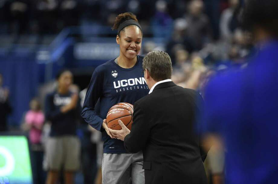 UConn's Azura Stevens receives a ball from coach Geno Auriemma in recognition of reaching 1,000 career points before Sunday's game against Notre Dame. Photo: Jessica Hill / Associated Press / AP2017