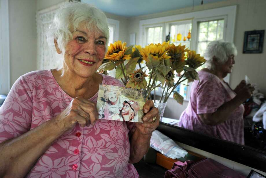 Jeanne Harrison, who died this weekend, holds a photo from her time training as a clown under the tutelage of Wavy Gravy Tuesday, July 28, 2015, at her home in Fairfield, Conn. Most local residents know Harrison for her part painting the town's fire hydrants to look like Redcoat soldiers. Photo: File Photo / Hearst Connecticut Media / Connecticut Post