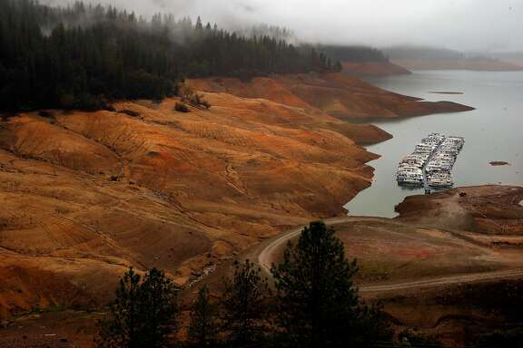 Light rain falls across the area as houseboats sit idle at Bridge Bay Resort at Shasta Lake, Calif., on Wednesday December 9, 2015, where the current water level is at twenty nine percent full.
