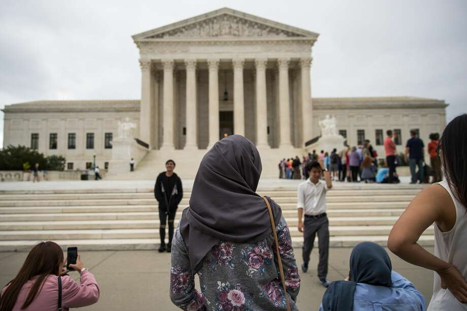 A woman wearing a hijab stands outside the U.S. Supreme Court, October 11, 2017 in Washington, DC. On Tuesday, the U.S. Supreme Court dismissed one of two cases challenging the Trump administration's effort to restrict travel from mostly Muslim countries. The court dismissed the case because the travel ban has since been replaced with a new version of the administration's controversial travel restriction. (Photo by Drew Angerer/Getty Images) Photo: Drew Angerer/Getty Images