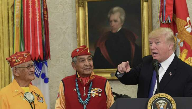 """With a portrait of President Andrew Jackson hanging in the background, President Donald Trump, right, speaks during a meeting with Navajo Code Talkers including Thomas Begay, left, and Peter MacDonald, center, in the Oval Office of the White House in Washington, Nov. 27. He used the occasion to once again Sen. Elizabeth Warren """"Pocahontas."""""""