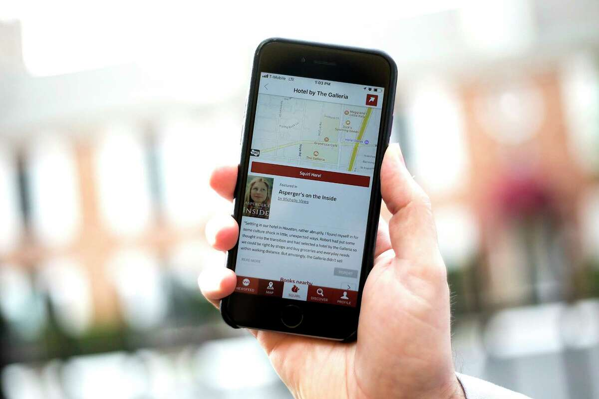 A sample on how the Squirl mobile app works in front of a hotel in Houston on Tuesday, Nov. 21, 2017. The mobile app uses GPS to call up books set in the same location as the user. ( Elizabeth Conley / Houston Chronicle )