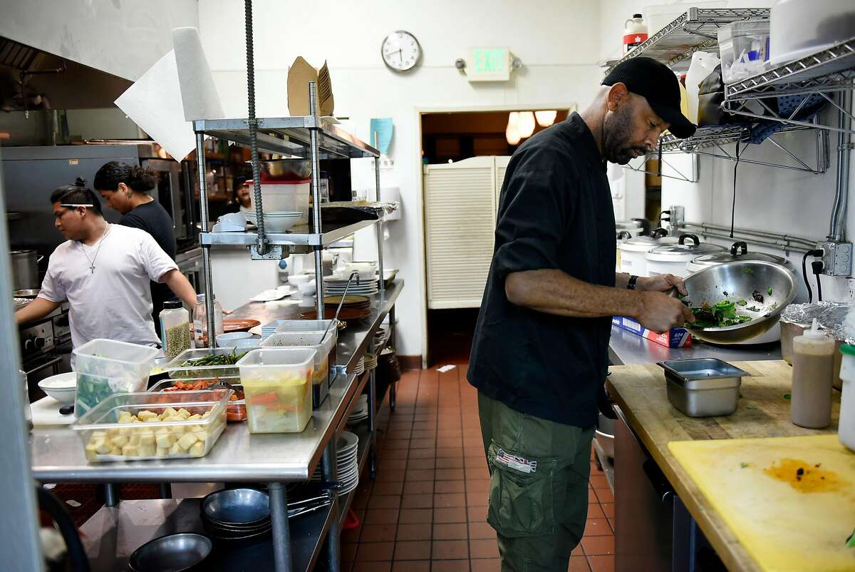 Owner Nigel Jones works with his staff in the kitchen of his restaurant Kingston 11, in Oakland, CA, on Thursday November 30, 2017.