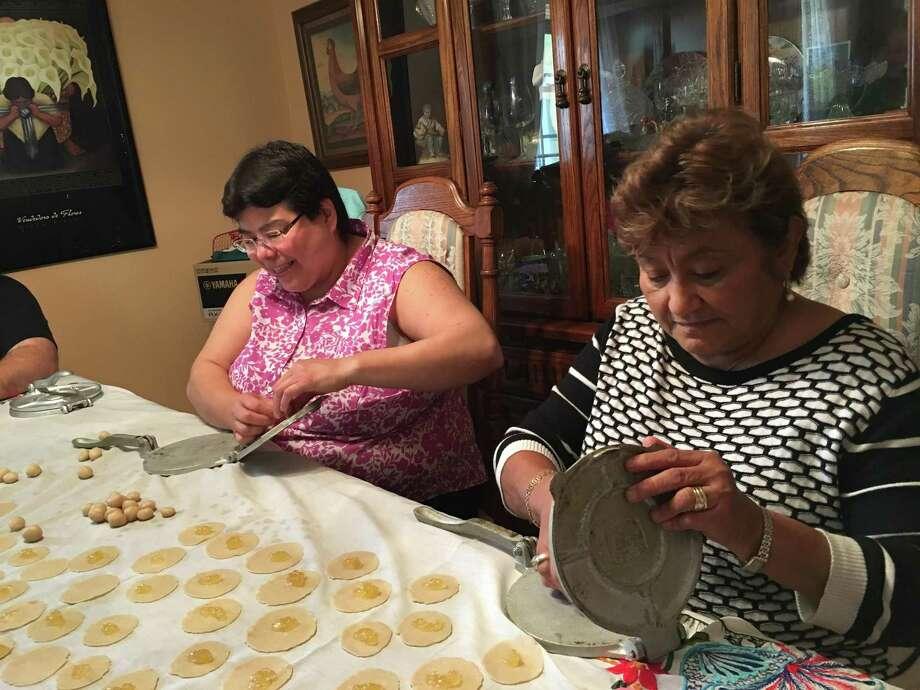 Corina Hernandez (from left) and Edilma Vallejo make pineapple empandadas, a family tradition during the holiday season. Photo: Courtesy Robert Adams