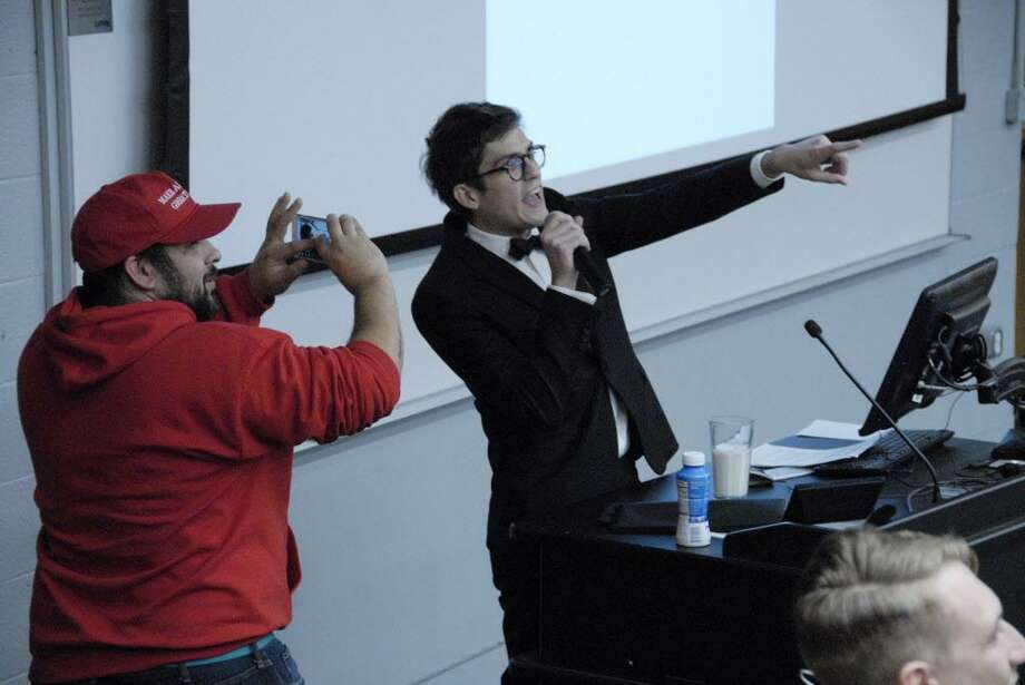 "In this Nov. 28, 2017 photo, Lucian Wintrich, White House correspondent for the right-wing blog Gateway Pundit, speaks at the University of Connecticut in Storrs, Conn. while being photographed by Salvatore ""Sal"" Cipolla. The conservative commentator was arrested and charged with breach of peace after an altercation during his speech titled ""It's OK To Be White."" (Rebecca Lurye/The Courant via AP) Photo: Rebecca Lurye/The Courant Via AP / The Courant"