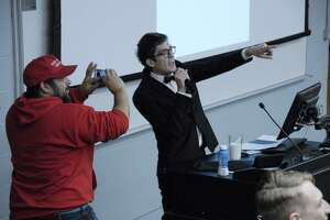 """In this Nov. 28, 2017 photo, Lucian Wintrich, White House correspondent for the right-wing blog Gateway Pundit, speaks at the University of Connecticut in Storrs, Conn. while being photographed by Salvatore """"Sal"""" Cipolla. The conservative commentator was arrested and charged with breach of peace after an altercation during his speech titled """"It's OK To Be White."""" (Rebecca Lurye/The Courant via AP)"""
