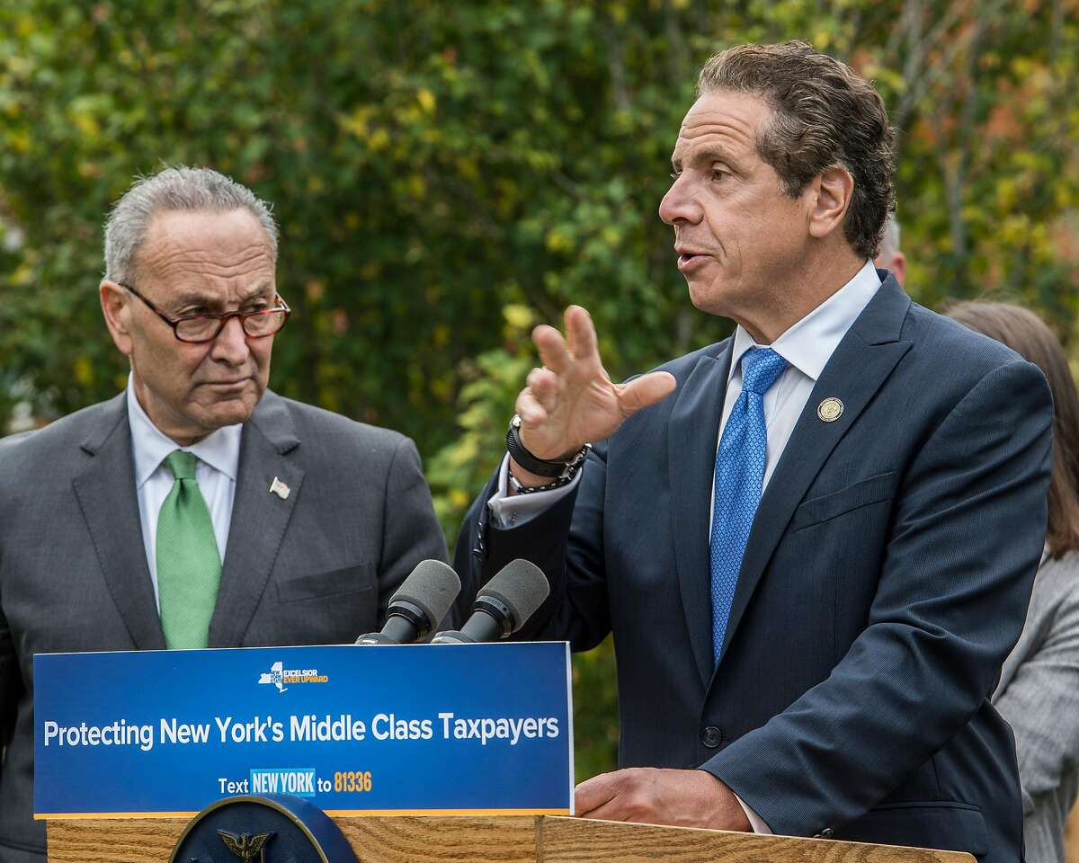Senator Charles Schumer, left and Governor Andrew Cuomo, right, joined forces on the front lawn of 85 University Street Monday Oct. 23, 2017 to call on New York Representatives to protect middle-class homeowners by opposing repeal of State and Local Tax deductions and any tax bill that proposes it at a press conference held in Bethlehem, N.Y. (Skip Dickstein/Times Union)