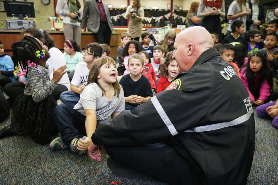Conroe Fire Chief Ken Kreger chats with students during the Operation Warm event on Monday, Dec. 5, 2016, at Rice Elementary in Conroe. Photo: Michael Minasi, Staff / © 2016 Houston Chronicle