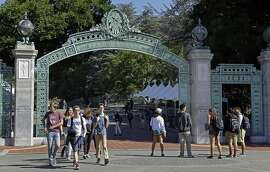 FILE - In this April 21, 2017, file photo, students walk past Sather Gate on the University of California, Berkeley campus in Berkeley, Calif.  With college classes starting soon, ideally you've made all your payments and are ready to settle in. But if you're still looking for financial aid to help cover your tuition, you'll have to move fast.  (AP Photo/Ben Margot, File)