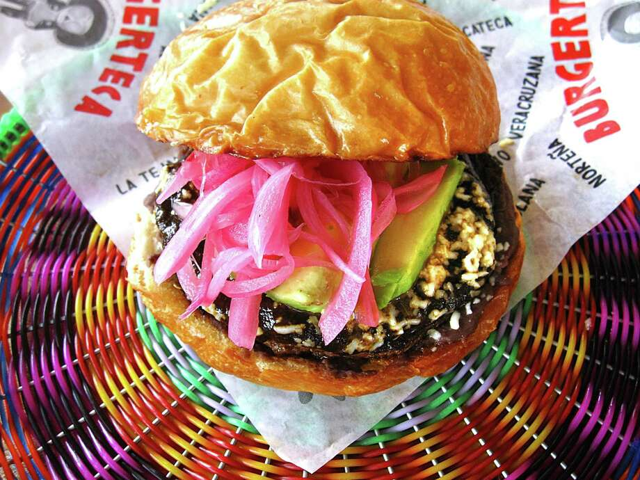Oaxaca burger with mole negro, black beans, pickled onions, avocado and queso fresco from Burgerteca, the new Mexican-inspired burger shop in Southtown from chef Johnny Hernandez. Photo: Mike Sutter /San Antonio Express-News
