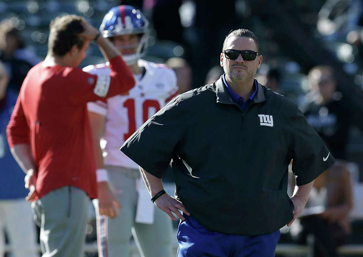 FILE - In this Dec. 3, 2017, file photo, New York Giants head coach Ben McAdoo is shown in front of quarterback Eli Manning (10) before an NFL football game against the Oakland Raiders, in Oakland, Calif. A person familiar with the situation says Ben McAdoo has been fired as coach of the New York Giants and Jerry Reese is out as general manager less than a year after taking the team to the playoffs for the first time since 2011. McAdoo and Reese were fired Monday, Dec. 4, 2017, a day after the Giants were beaten in Oakland and dropped to 2-10, according to the person who spoke on condition of anonymity because the team had not made an official announcement. (AP Photo/Ben Margot, File) ORG XMIT: NY181