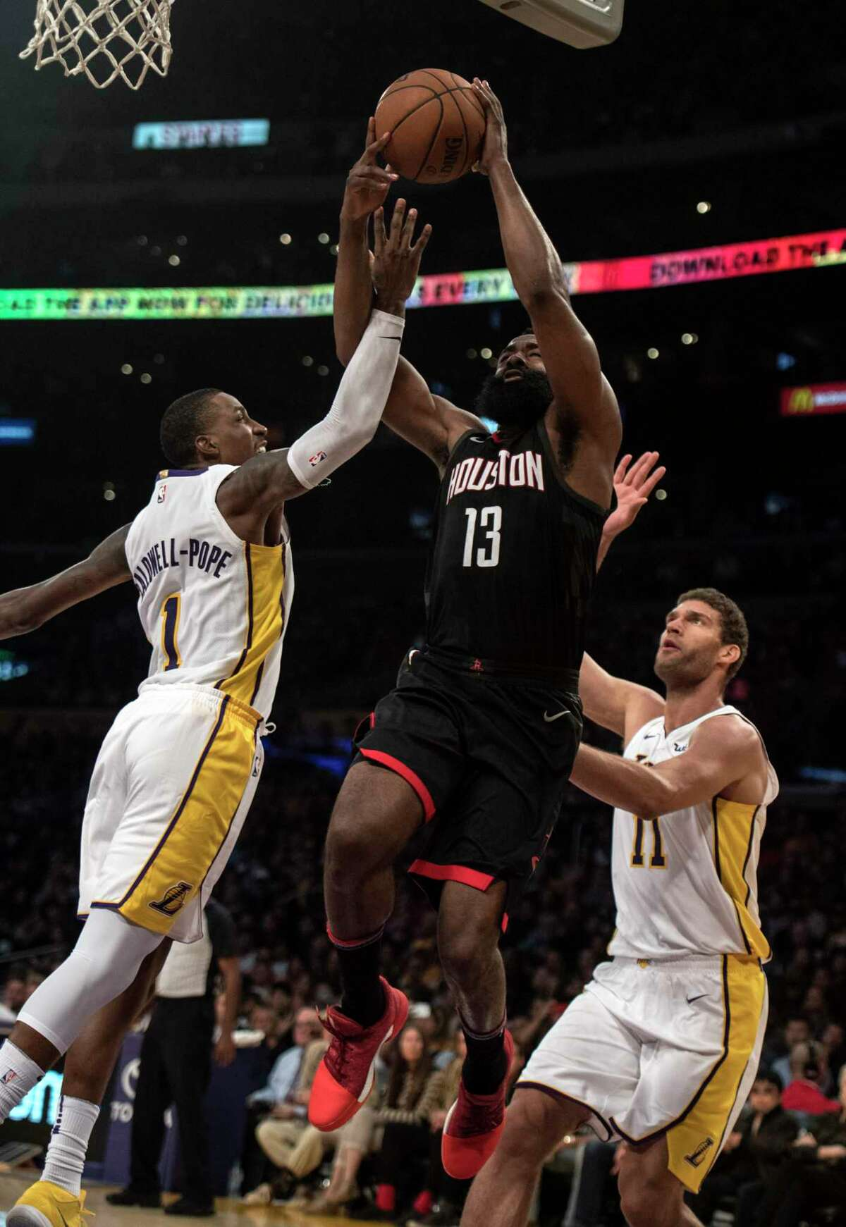 Houston Rockets guard James Harden (13) shoots under pressure as Los Angeles Lakers guard Kentavious Caldwell-Pope, left, and center Brook Lopez (11) defend him during the first half of an NBA basketball game Sunday, Dec. 3, 2017, in Los Angeles. (AP Photo/Kyusung Gong)