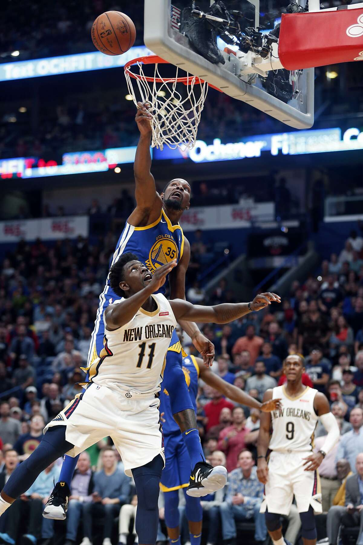 Golden State Warriors forward Kevin Durant (35) blocks a shot by New Orleans Pelicans guard Jrue Holiday (11) but was called for basket interference, in the second half of an NBA basketball game in New Orleans, Monday, Dec. 4, 2017. The Warriors won 125-115.