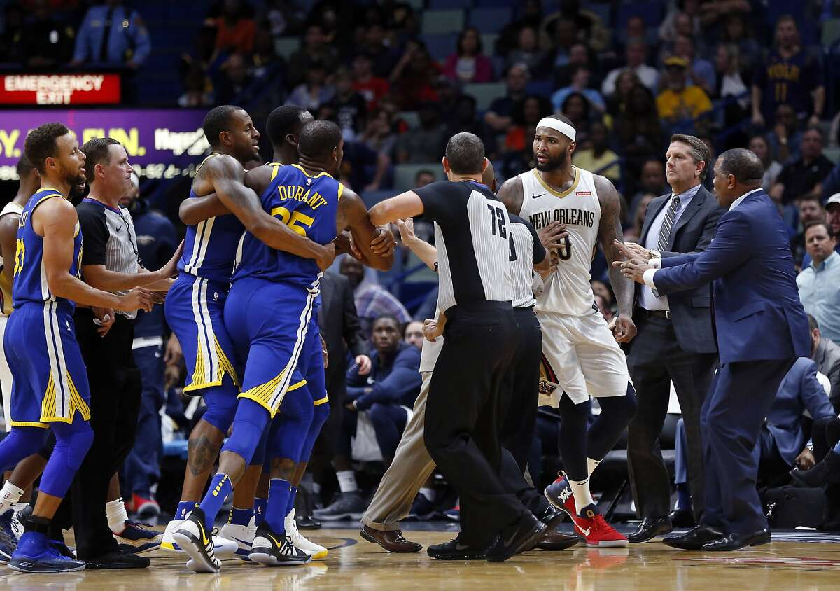 Golden State Warriors forward Kevin Durant and New Orleans Pelicans center DeMarcus Cousins (0) are restrained while going after each other during a scuffle in the second half of an NBA basketball game in New Orleans, Monday, Dec. 4, 2017. Both players were ejected from the game.
