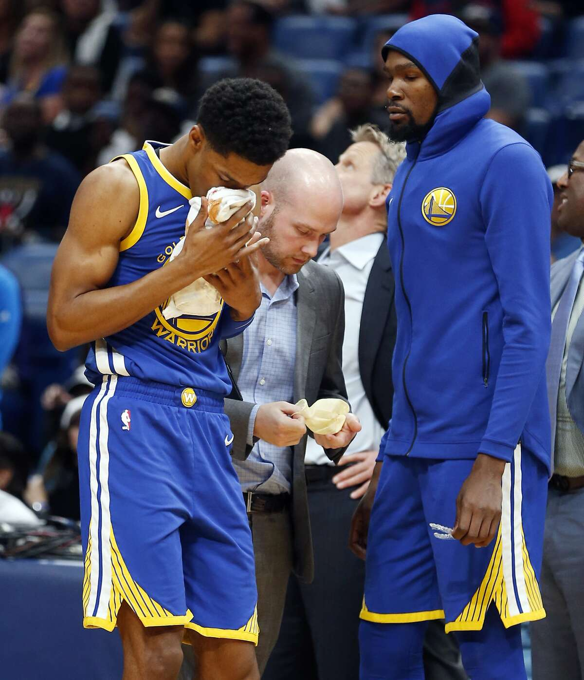Golden State Warriors guard Patrick McCaw holds a towel to his nose after being hit in the first half of an NBA basketball game against the New Orleans Pelicans in New Orleans, Monday, Dec. 4, 2017. (AP Photo/Gerald Herbert)