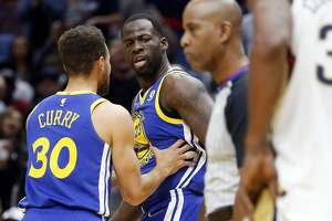 Golden State Warriors forward Draymond Green (23) is restrained by guard Stephen Curry (30) after being called for a technical foul for yelling at an official, in the first half of an NBA basketball game against the New Orleans Pelicans in New Orleans, Monday, Dec. 4, 2017. (AP Photo/Gerald Herbert)