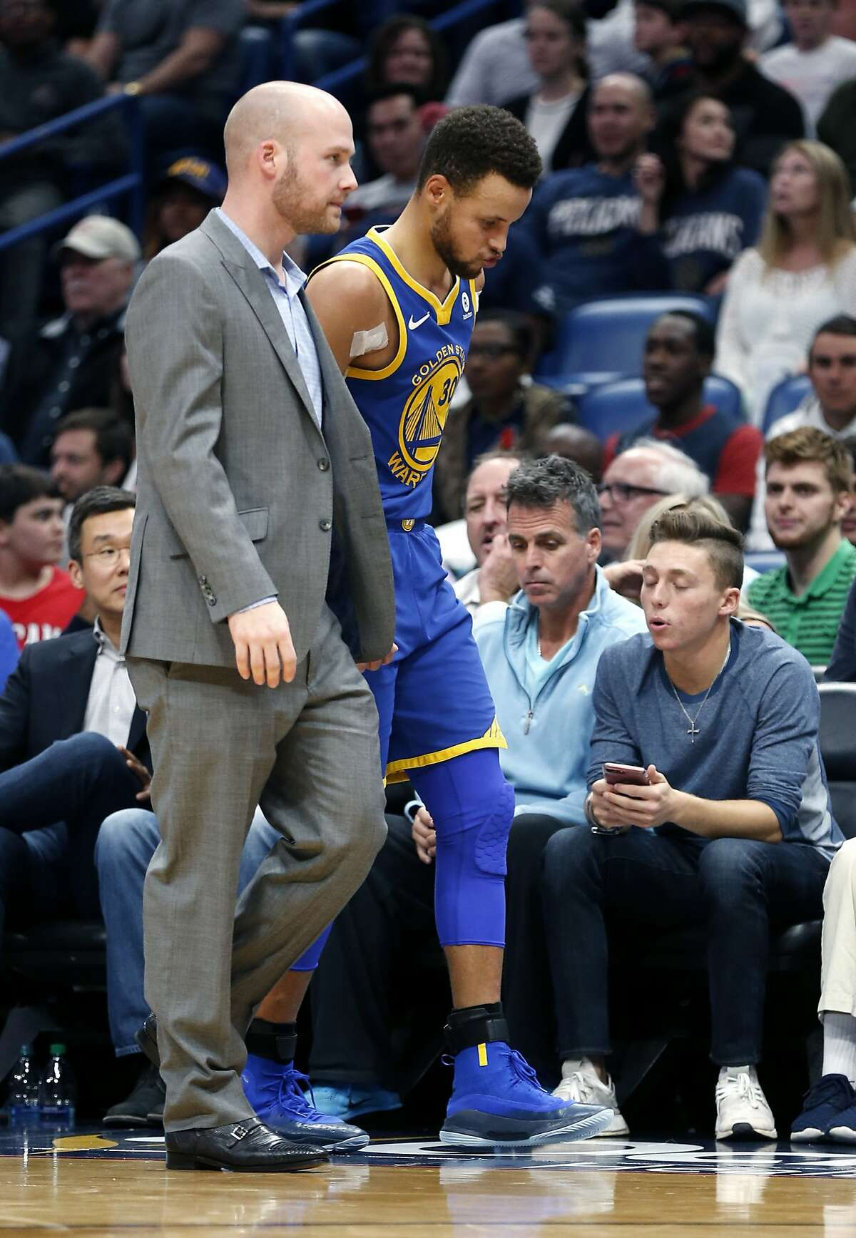 Golden State Warriors guard Stephen Curry limps off the court to the locker room in the second half of an NBA basketball game against the New Orleans Pelicans in New Orleans, Monday, Dec. 4, 2017. The Warriors won 125-115. (AP Photo/Gerald Herbert)