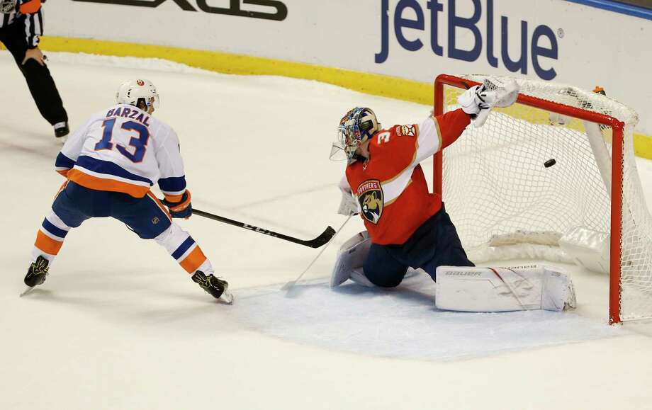 New York Islanders center Mathew Barzal (13) scores against Florida Panthers goalie James Reimer (34) during a shootout in an NHL hockey game, Monday, Dec. 4, 2017, in Sunrise, Fla. The Islanders defeated the Panthers 5-4 in a shootout. (AP Photo/Wilfredo Lee) ORG XMIT: FLWL110 Photo: Wilfredo Lee / Copyright 2017 The Associated Press. All rights reserved.