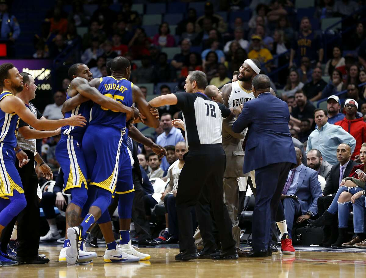 Golden State Warriors forward Kevin Durant and New Orleans Pelicans center DeMarcus Cousins (0) are restrained while going after each other during a scuffle in the second half of an NBA basketball game in New Orleans, Monday, Dec. 4, 2017. Both players were ejected from the game, and the Warriors won 125-115.