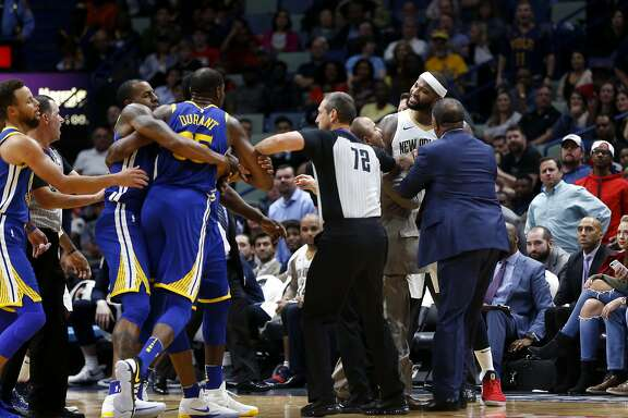 Golden State Warriors forward Kevin Durant and New Orleans Pelicans center DeMarcus Cousins (0) are restrained while going after each other during a scuffle in the second half of an NBA basketball game in New Orleans, Monday, Dec. 4, 2017. Both players were ejected from the game, and the Warriors won 125-115. (AP Photo/Gerald Herbert)