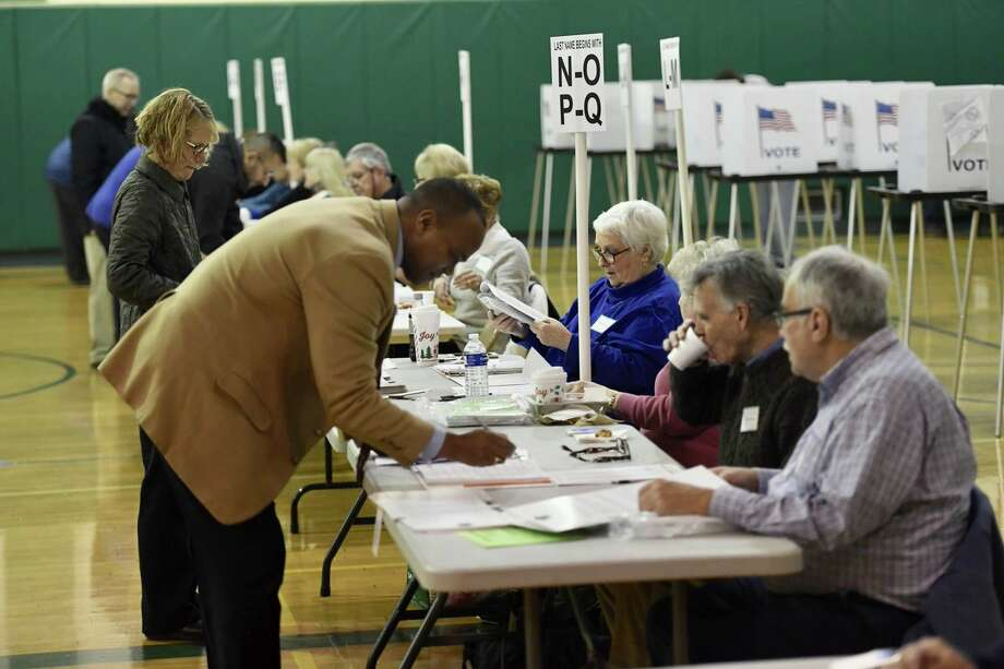 Shenendehowa School District Superintendent Oliver Robinson is among the first voters to sign in to cast a ballot in Tuesday's school land sale.  Photo: Skip Dickstein / Times Union